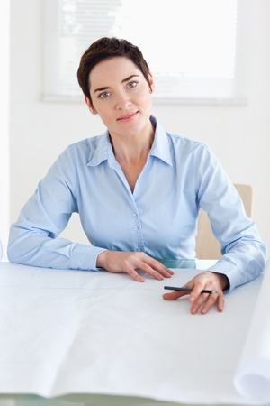 Working businesswoman with a architectural plan in an office photo