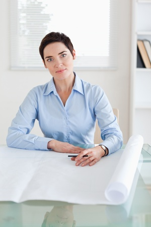 Working woman with a architectural plan in an office photo