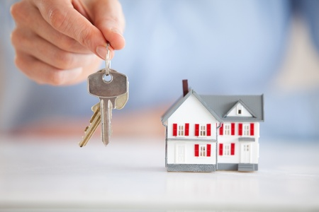 Woman holding keys next to a model house in an office Stock Photo - 11191061