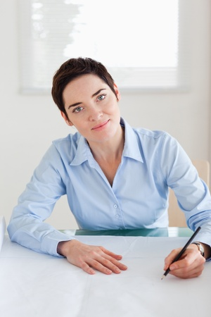 Charming woman with a architectural plan looking into the camera in an office photo