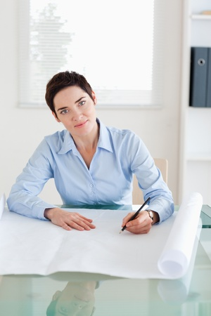 Smiling woman with a architectural plan looking into the camera in an office photo