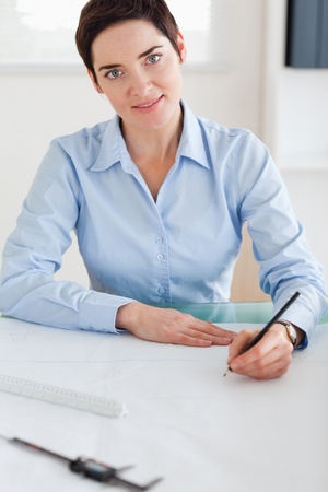 Woman with a architectural plan looking into the camera in an office photo