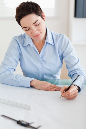 Woman working on an architectural plan in an office photo