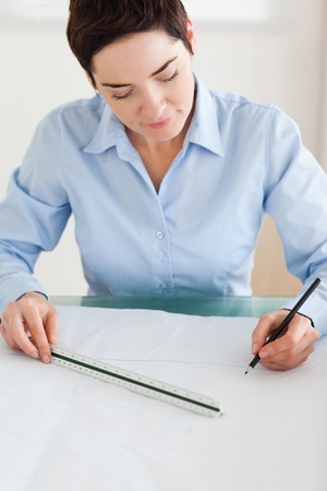 Gorgeous Woman working on an architectural plan in an office photo