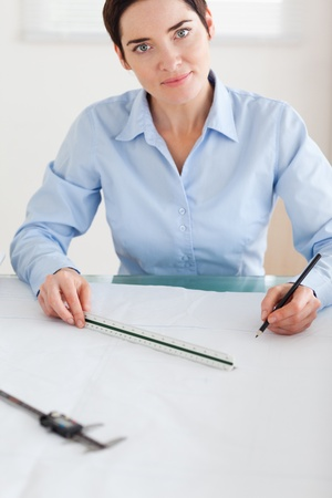 Gorgeous Woman working on an architectural plan looking into the camera in an office photo