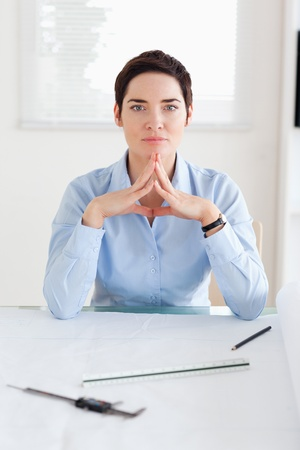 Thoughtful Woman with an architectural plan looking into the camera in an office photo