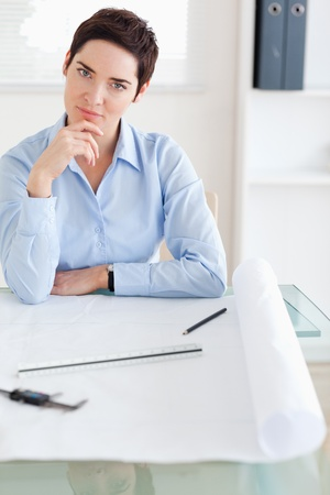 Thoughtful brunette Woman with an architectural plan looking into the camera in an office photo