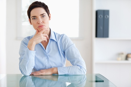 Thoughtful Businesswoman sitting behind a desk in an office photo