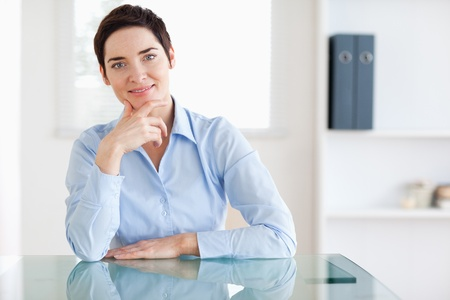 Smiling Businesswoman sitting behind a desk in an office photo
