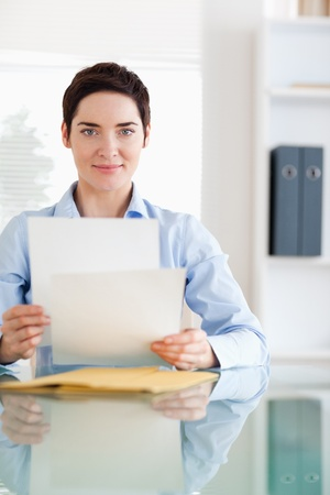 Portrait of a Businesswoman sitting behind a desk with papers in an office photo