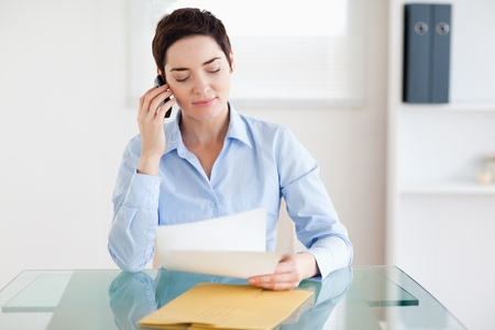 Portrait of a brunette Businesswoman sitting behind a desk with papers on the phone in an office photo