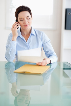 Businesswoman sitting behind a desk with papers on the phone in an office photo