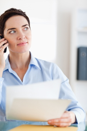 Close up of a Businesswoman with papers on the phone in an office photo