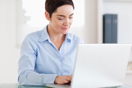 Smiling Businesswoman with a laptop in an office photo