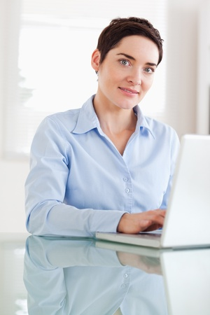 Brunette businesswoman with a laptop looking at the camera in an office Stock Photo - 11213353