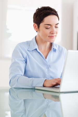 Brunette businesswoman with a laptop in an office photo