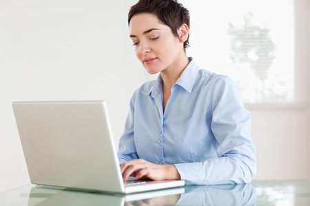 Charming short-haired businesswoman with a laptop in an office photo