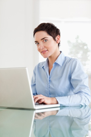 Short-haired businesswoman with a laptop looking into the camera in an office photo