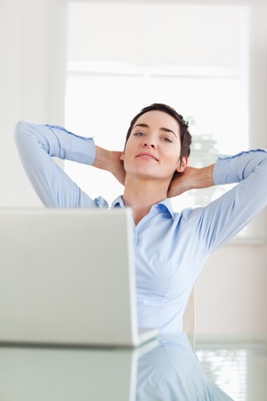 Relaxed businesswoman with a laptop looking into the camera in an office photo