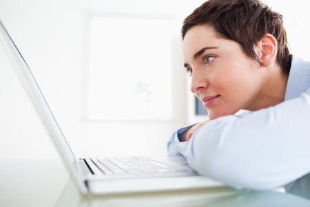 Brunette short-haired businesswoman with a laptop in an office photo
