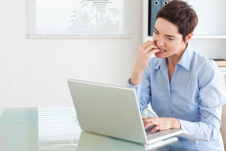 Angry brunette Businesswoman with a laptop in an office photo