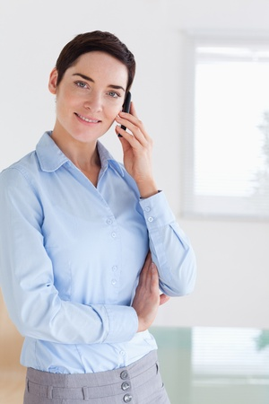 Smiling brunette businesswoman on the phone in her office Stock Photo - 11191346