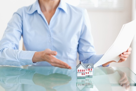 Woman holding papers showing a model house in her office Stock Photo - 11213024