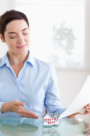 Smiling Woman holding papers showing a model house in an office Stock Photo - 11214420