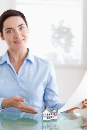 Charming Woman holding papers showing a model house in an office Stock Photo - 11214317