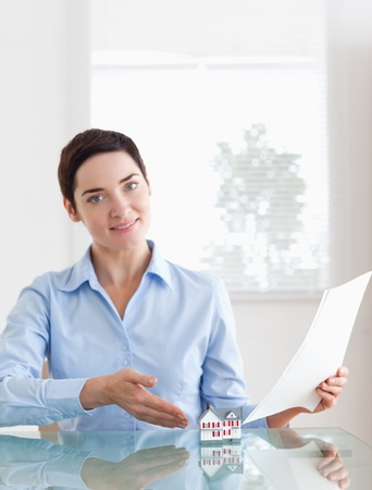 Gorgeous Woman holding papers showing a model house in an office Stock Photo - 11226686