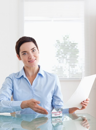 Brunette Woman holding papers showing a model house in an office Stock Photo - 11226099