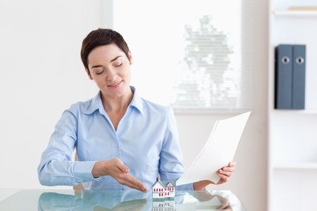 Short-haired Woman holding papers showing a model house in her office Stock Photo - 11214463