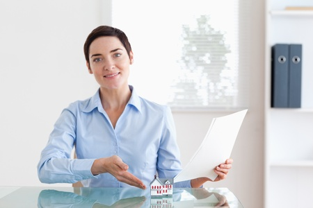Short-haired Woman holding papers pointing at a model house in an office Stock Photo - 11214323