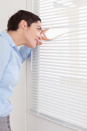Brunette woman peeking out a window in an office photo