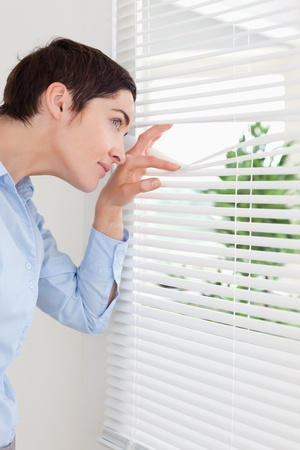 Cute woman peeking out a window in an office photo