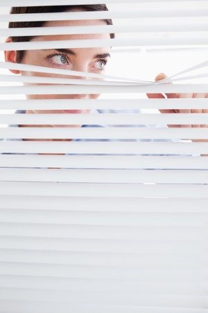 Curious brunette Woman peeking out of a window in an office photo