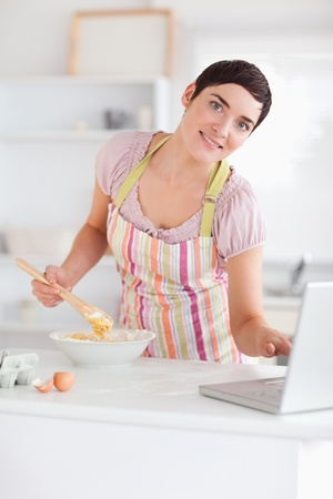 Smiling Woman looking at a receipt on a laptop in a kitchen photo