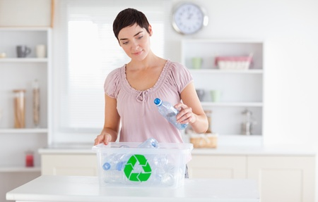 Woman putting bottles in a recycling box in a kitchen photo