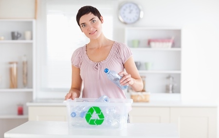 Cute Woman putting bottles in a recycling box in a kitchen photo