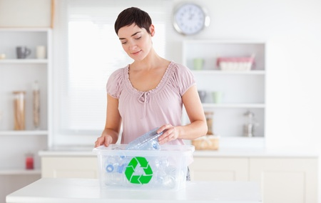 Charming Woman putting bottles in a recycling box in a kitchen photo