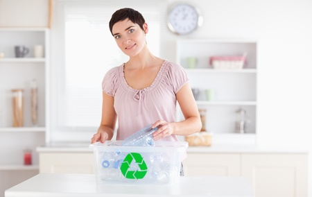 Smiling Woman putting bottles in a recycling box in a kitchen photo