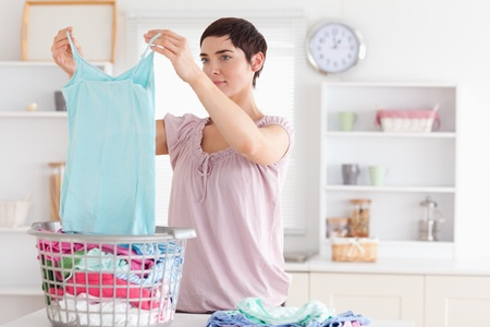chore: Woman folding clothes in a utility room Stock Photo