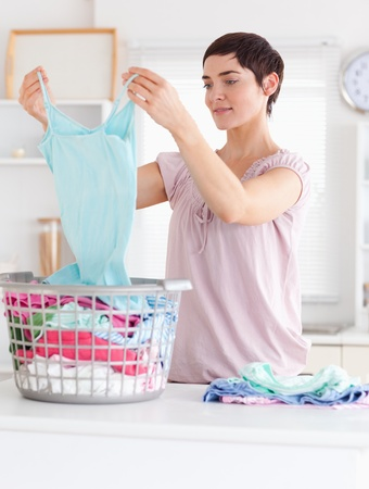 Cute Woman folding clothes in a utility room photo
