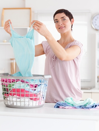 Charming Woman folding clothes in a utility room photo