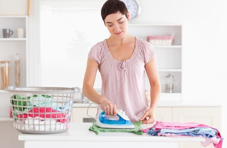 Woman ironing clothes in a utility room photo