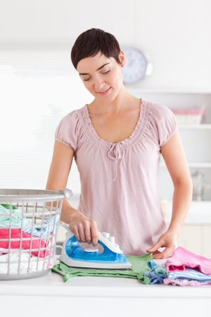 Charming Woman ironing clothes in a utility room photo