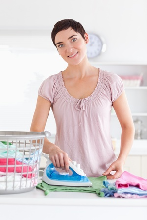 Smiling Woman ironing clothes in a utility room photo