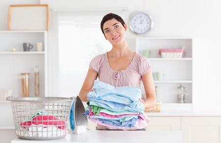Woman with a pile of clothes in a utility room photo