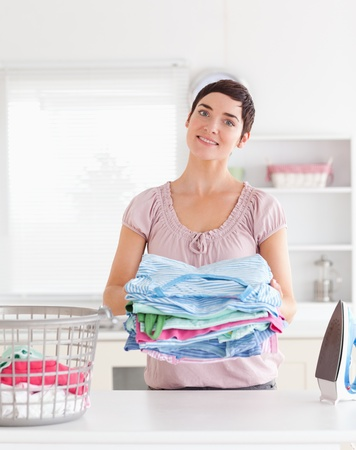 Charming Woman with a pile of clothes in a utility room photo