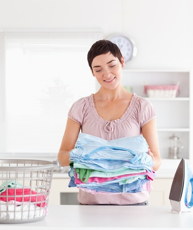 Smiling Woman with a pile of clothes in a utility room photo